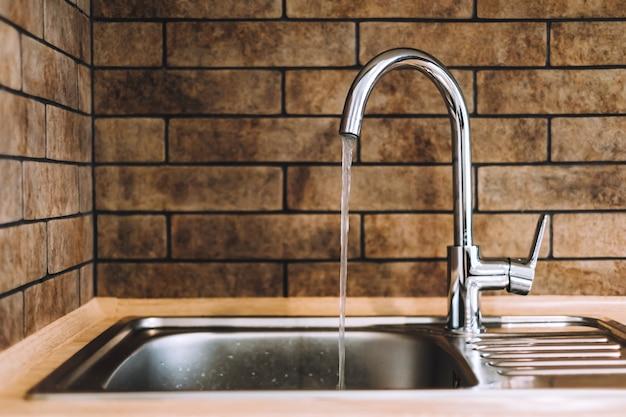 Torneira prateada com água corrente na cozinha.