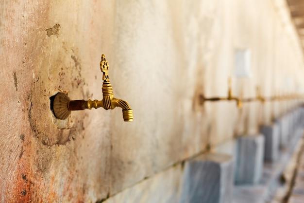 Torneiras com água para lavar os pés para a entrada da mesquita.