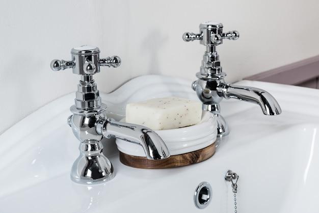 Torneiras de aço novas e modernas com pia de cerâmica no banheiro