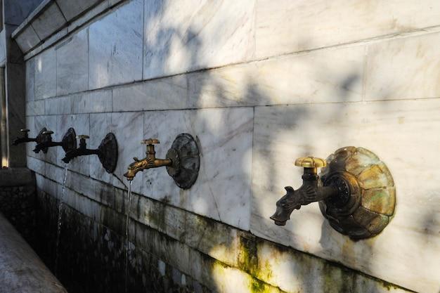Torneiras de bronze na cidade com água potável