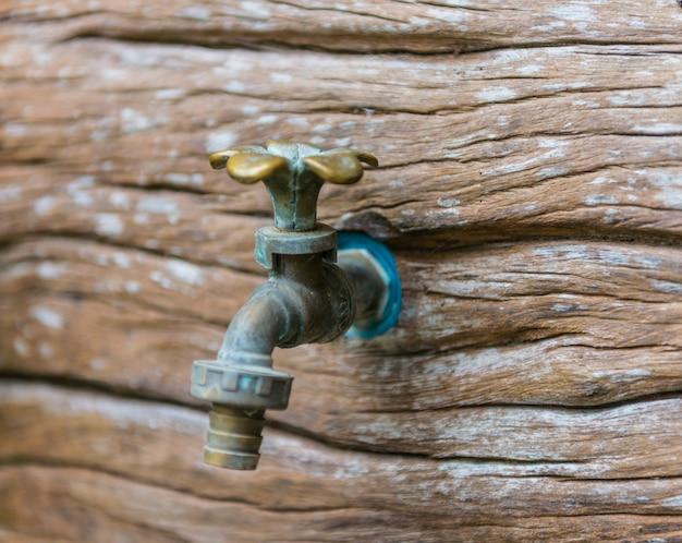 Torneiras de latão na parede de madeira
