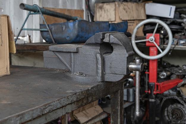 Torno de banco velho do metal na tabela de aço na oficina. abraçadeiras de metal.