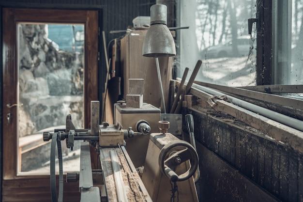 Torno velho em pé de um carpinteiro velho por uma janela coberta com poeira e teias de aranha
