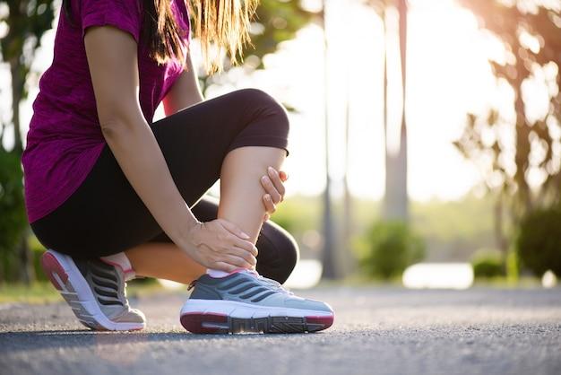 Tornozelo torcido. jovem mulher que sofre de uma lesão no tornozelo durante o exercício