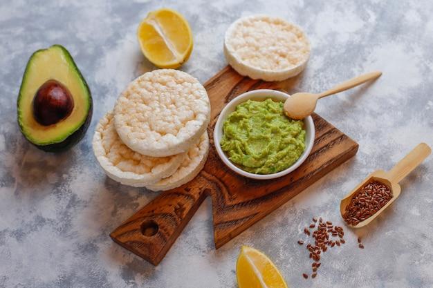 Torrada aberta de abacate com pão de arroz, fatia de limão, fatias de abacate, vista superior de sementes.
