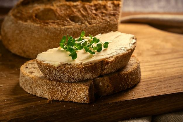 Torrada artesanal em fatias de pão com manteiga e brócolis microgreen na tábua de madeira