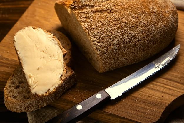 Torrada artesanal em fatias de pão com manteiga em uma tábua de madeira com faca