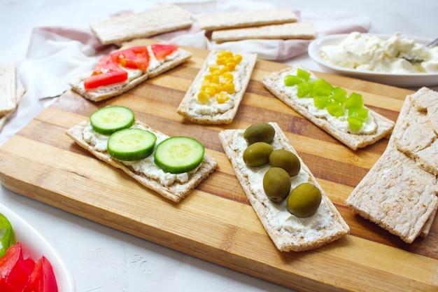 Torrada caseira com queijo cottage e azeitonas verdes, fatias de repolho, tomate, milho, pimenta verde na tábua. conceito de comida saudável, vista superior. configuração plana