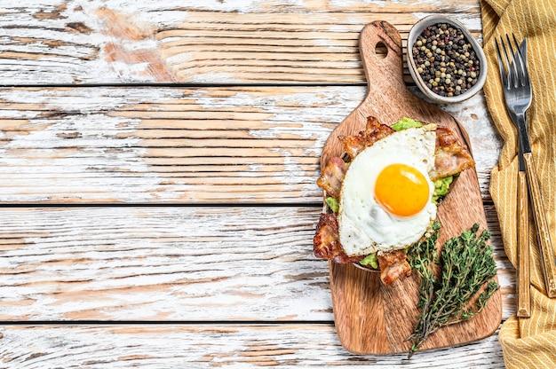 Torrada com abacate, bacon frito e ovo. fundo de madeira branco. vista do topo. copie o espaço.