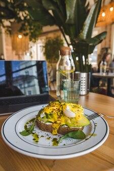 Torrada com abacate e ovos no prato em restaurante de cores marrons copie o espaço