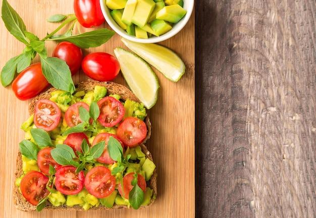Torrada com abacate, tomate e manjericão em madeira rústica