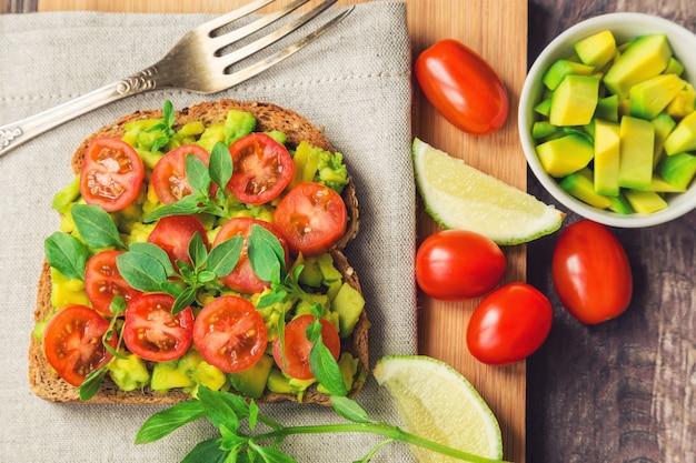 Torrada com abacate, tomate e manjericão em mesa de madeira rústica