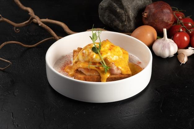 Torrada com bacon e ovo benedict. café da manhã quente feito de ovos cozidos, carne de porco, pão torrado e molho de queijo com especiarias