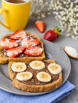 Torrada com chocolate e frutas em um prato cinza. morangos e bananas na mesa de pedra da cozinha