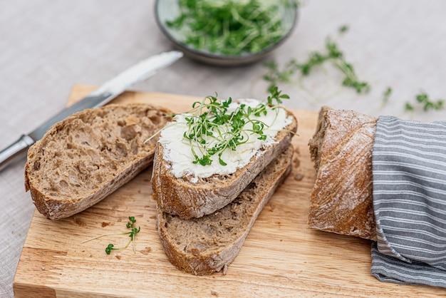 Torrada com cream cheese e micro salada, conceito de comida saudável