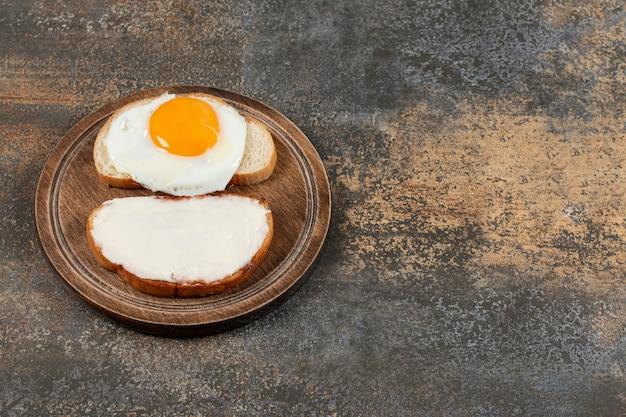 Torrada com cream cheese e ovo na tábua de madeira.