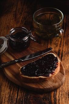 Torrada com geléia de frutas vermelhas na tábua e xícara de chá verde em ambiente rústico