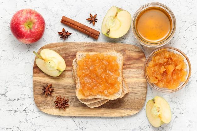Torrada com geléia de maçã na tábua de madeira com pote de mel