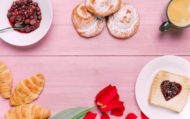 Torrada com geléia em forma de coração com tulipa, frutas e pãezinhos