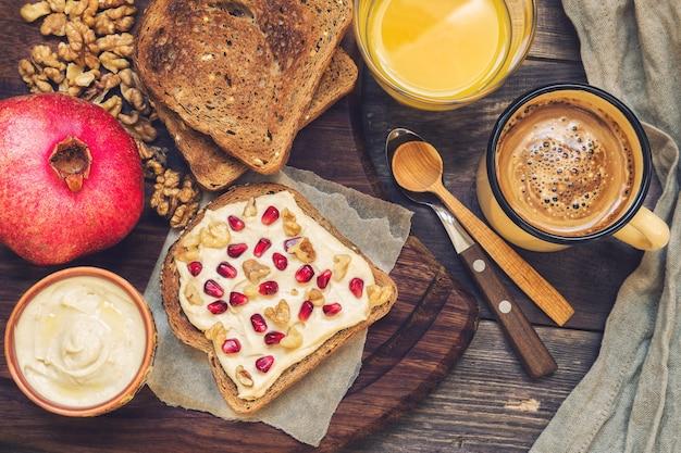 Torrada com homus, nozes e romã em madeira rústica. café da manhã saudável.
