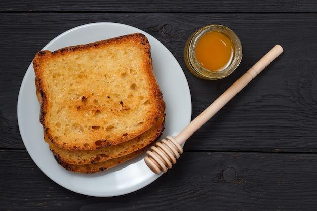 Torrada com leite e um pote de mel em um fundo preto de madeira