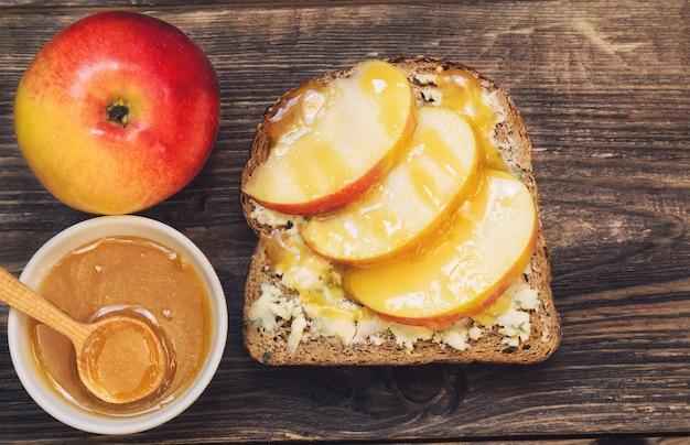 Torrada com maçã, mel e queijo gorgonzola em fundo de madeira rústico. café da manhã saudável.