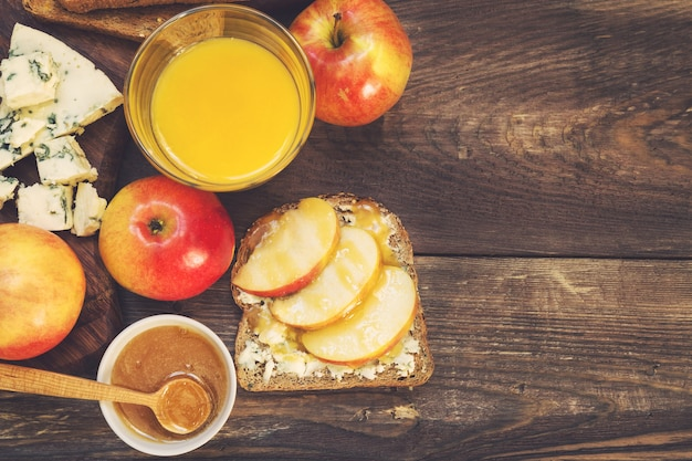 Torrada com maçã, mel e queijo gorgonzola numa superfície de madeira rústica. café da manhã saudável.