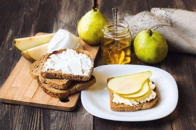 Torrada com pêra, ricota e mel em fundo de madeira rústico com ingredientes. café da manhã saudável.