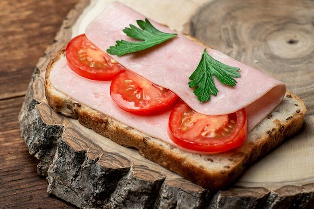 Torrada com presunto e tomate em um fundo de madeira.
