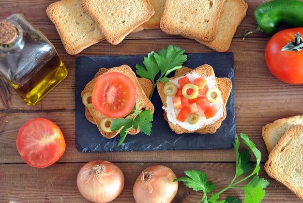 Torrada com tomate, azeite, azeitonas verdes na mesa de madeira