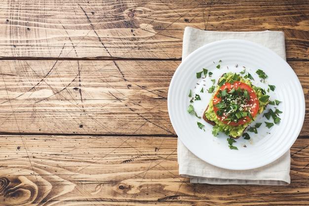 Torrada de abacate. brinde saudável com puré de abacate e tomate em um prato.