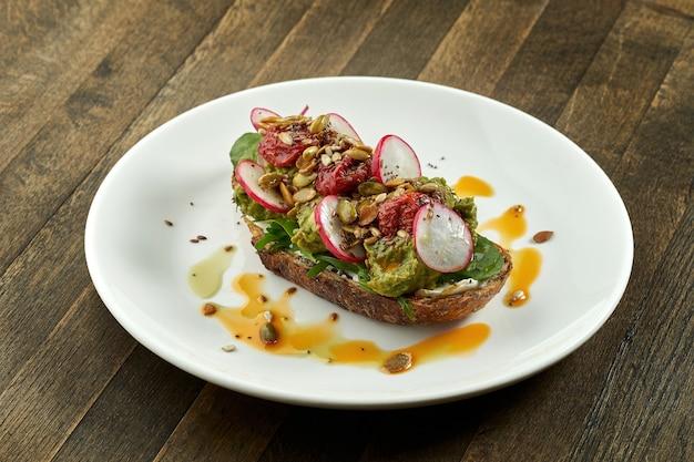 Torrada de abacate com guacamole, rabanete, tomate seco e sementes no pão de centeio, servido em um prato branco na mesa de madeira