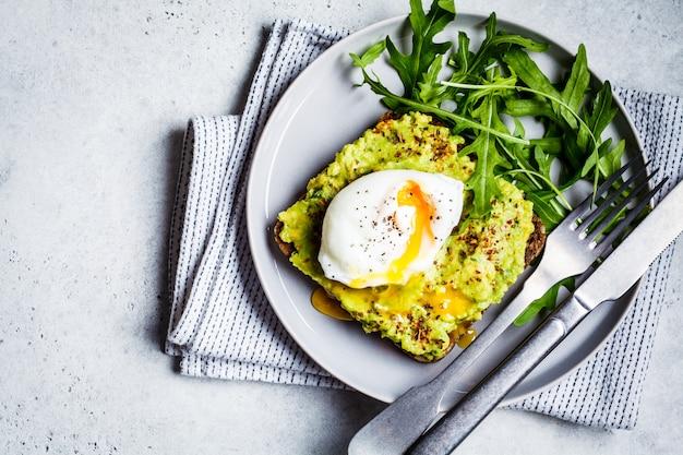 Torrada de abacate com ovo escalfado na chapa cinza. conceito de comida vegetariana saudável.