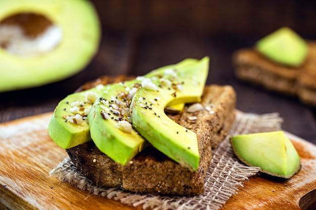 Torrada de abacate saudável com pão de centeio, fatias de abacate, rúcula e sementes. sanduíches vegetarianos. dieta à base de ervas.