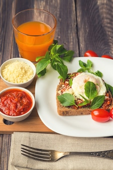 Torrada de café da manhã com ovo pochê, molho de tomate, manjericão e queijo parmesão em superfície de madeira rústica