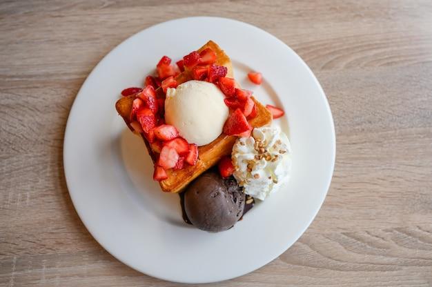 Torrada de mel com fatias de morango, baunilha, sorvete de chocolate amargo e chantilly em prato branco