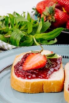 Torrada de morango de lado vista pão branco com geléia de morango e hortelã em cima da mesa
