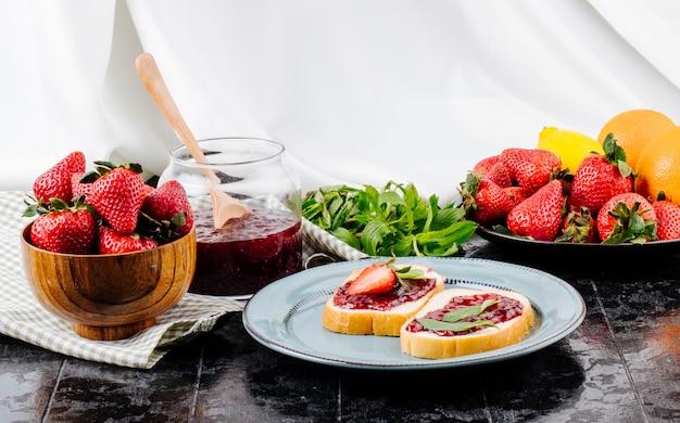 Torrada de morango vista lateral pão branco com geléia de morango menta laranja e morango fresco em cima da mesa