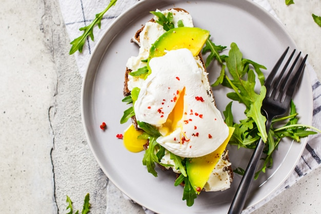 Torrada de ovo escalfado com abacate, queijo creme e pão de centeio na chapa cinza. conceito de comida saudável.
