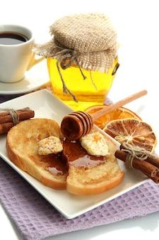 Torrada de pão branco com mel e café, isolado no branco