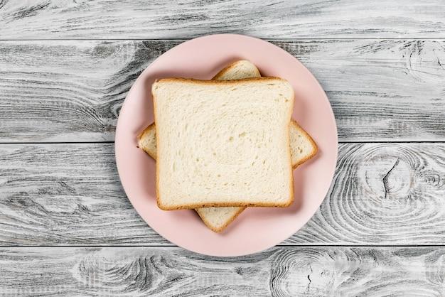 Torrada de pão branco na placa rosa na mesa de madeira.