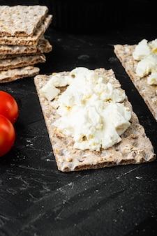 Torrada de pão caseiro com queijo cottage, na mesa de pedra preta escura