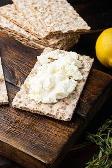 Torrada de pão caseiro com queijo cottage, na velha mesa de madeira escura