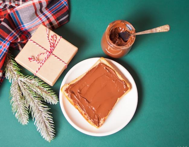 Torrada de pão com creme de chocolate, caixa de presente e ramo de pinheiro
