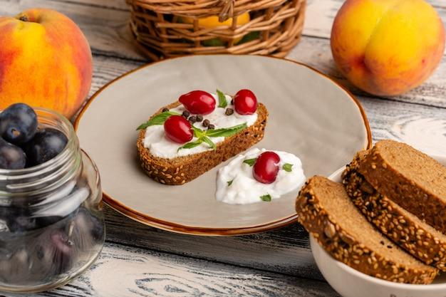 Torrada de pão com creme de leite e dogwood na mesa cinza lanche torrada pão refeição comida