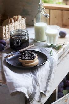 Torrada de pão com geléia de ameixa, servida com leite e ameixas. estilo rústico.