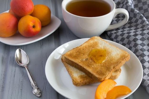 Torrada de pão com geléia de damasco e chá