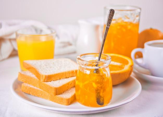 Torrada de pão com geléia de laranja, copos de suco de laranja na mesa branca conceito de café da manhã.