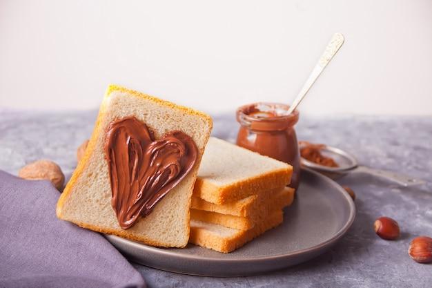 Torrada de pão com manteiga de creme de chocolate em forma de coração, pote de creme de chocolate