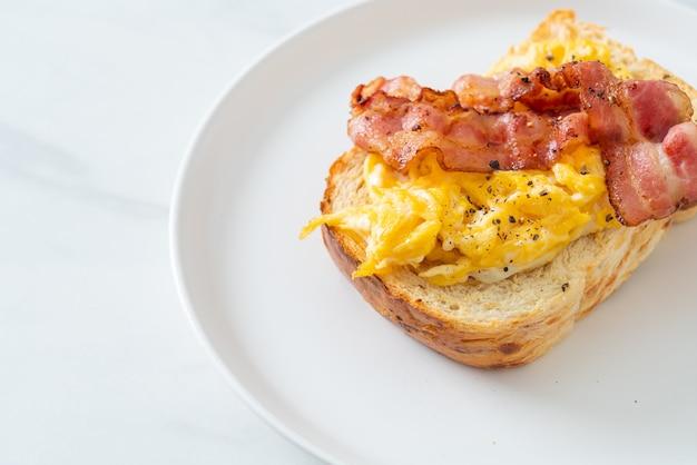 Torrada de pão com ovo mexido e bacon em prato branco